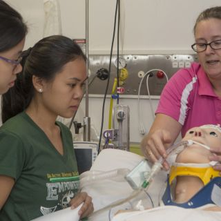 UC nursing student Lori Delaney showing the manikin to UST students