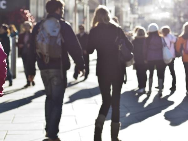 People walk along a sunlit street