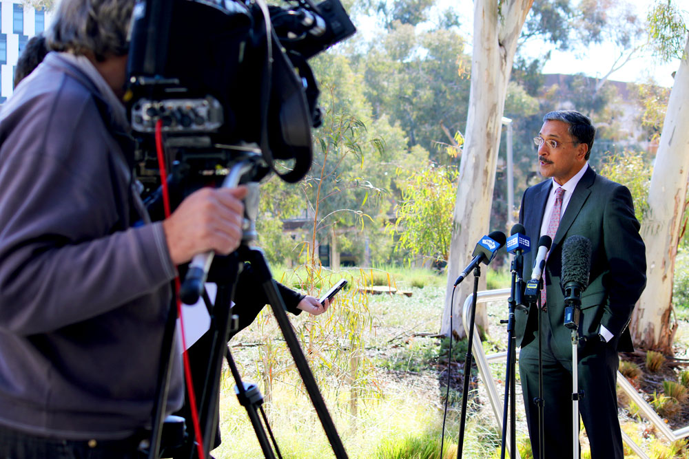 Vice-Chancellor Professor Deep Saini stands in front of gathered media cameras to respond to the AHRC report