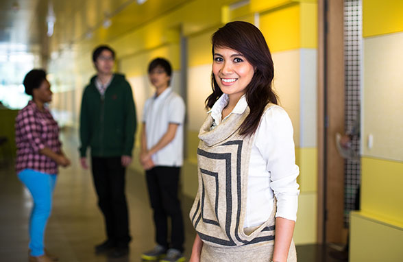 A student smiles in a corridor