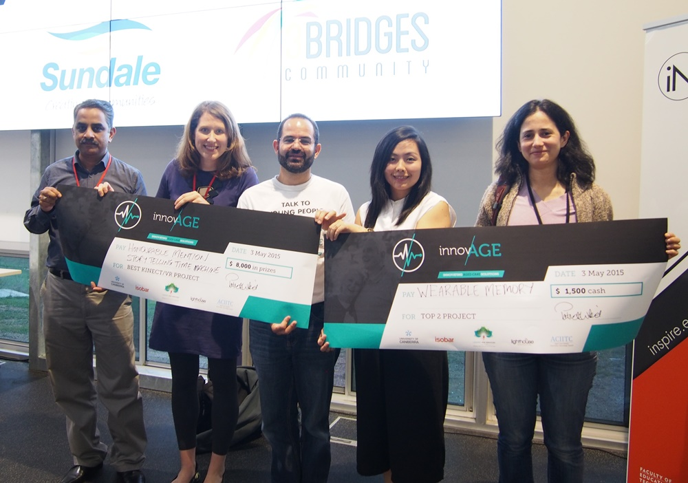 University of Canberra researchers holding their prize cheques after winning three prizes at the InnovAGE hackathon