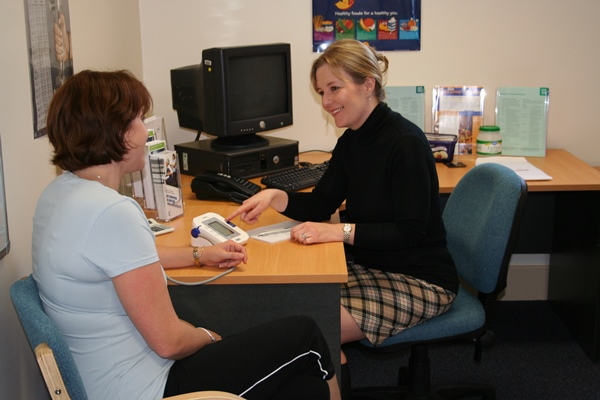 A female General Practitioner speaks with a patient while measuring her blood pressure