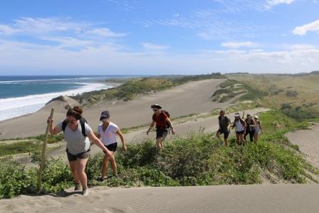Students climb a tall sand dune overlooking the ocean