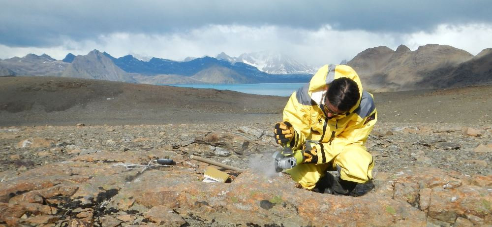 Dr Duanne White cuts a rock sample in front of the mountainous landscape of South Georgia Island