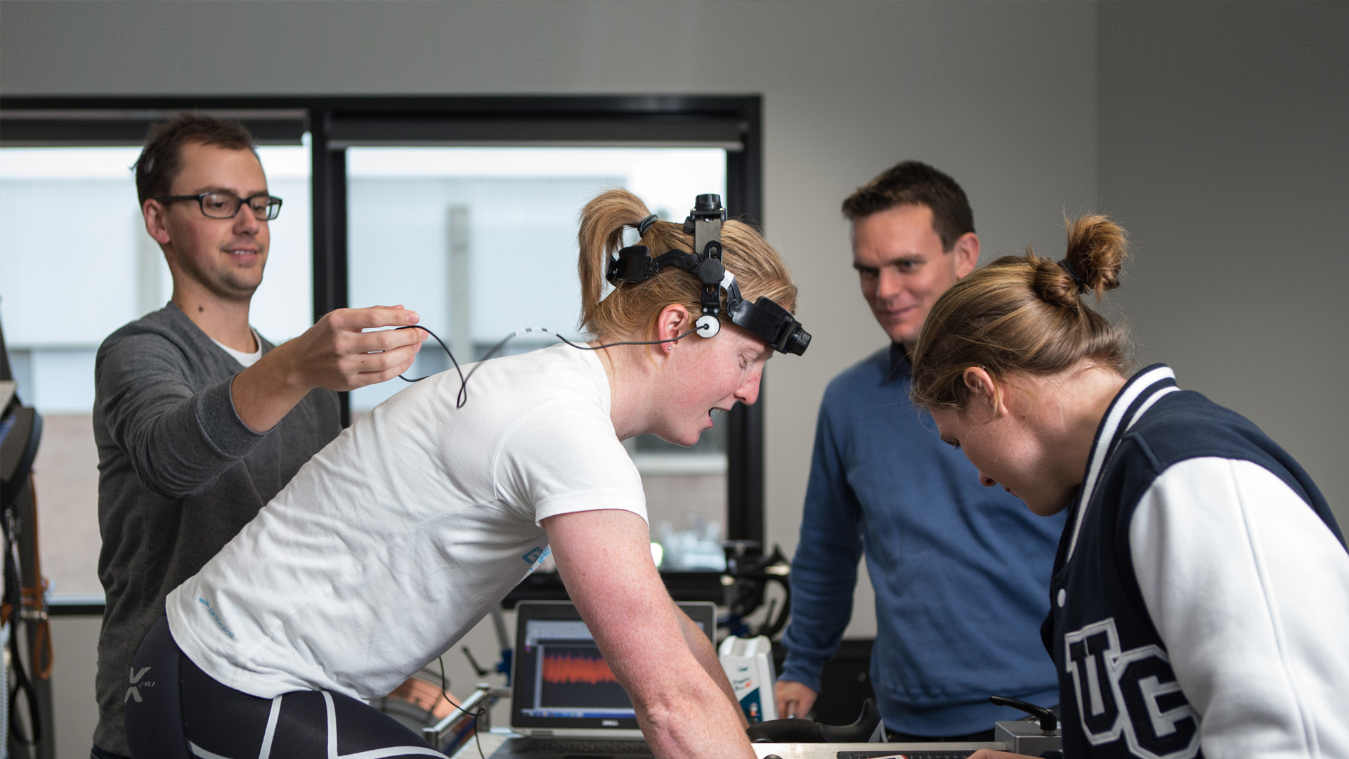 Photo of students working with athlete on static exercise bicycle