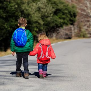 Two children wearing winter jackets are walking along a road
