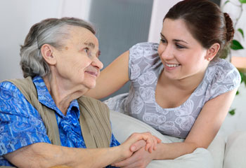 An older woman holds the hand of a younger carer