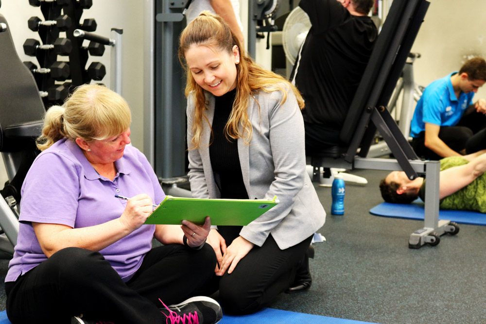 Kellie Toohey talks with a participant about her progress during the exercise program