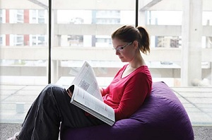 Student reading comfortably in front of accommodation window