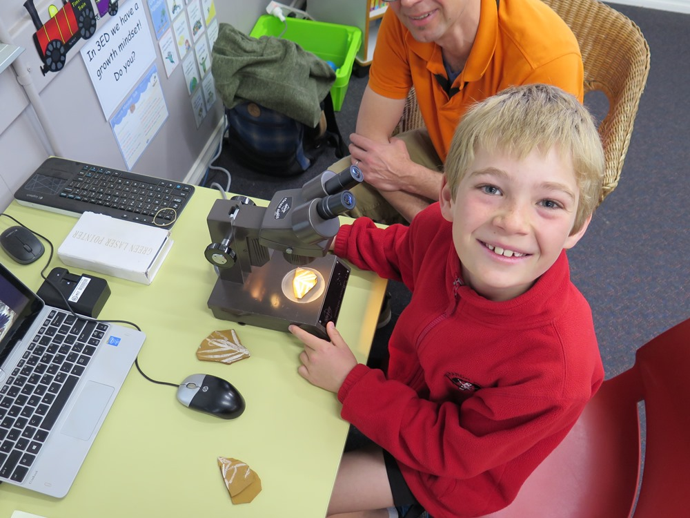 An Aranda Primary School student smiles while using a microscope to examine a fossilised plant