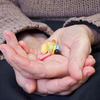 An older person holds a selection of pills and vitamins in their hands