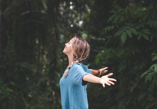 A woman with her arms wide open breathin in fresh air in a forest location. She is a patient of the counselling service at UC Health Clinics.