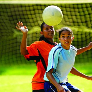 Two teenage girls are playing soccer on opposing teams as a ball flies toward the goal net.