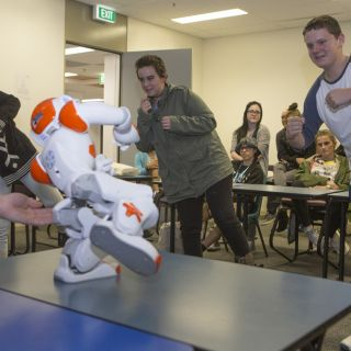 Taylan Bruce, Teagan Kindeysides and Kai Batten from Wagga's Mount Austin High School take a Tai Chi lesson from the University of Canberra's robot Ardie. Photo: Michelle McAulay