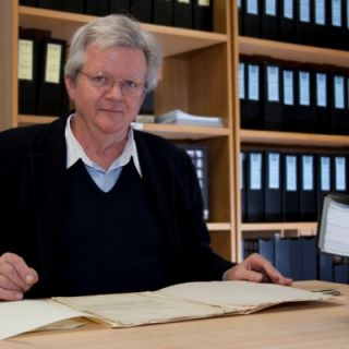 Dr Peter Copeman sits at a desk in his office
