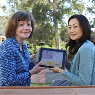 Sora Park and Sally Burford hold an iPad used in a study to see if mobile devices can help people with type 2 diabetes better manage and improve their health