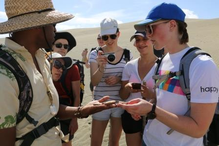 A guide shows UC students the remains of ancient pottery uncovered at the site of Fiji's first settlement