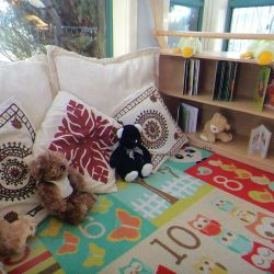 a comfortable area with cushions, teddies, books