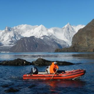 Scientists studing the landscape of South Georgia Island travel across one of the islands waterways