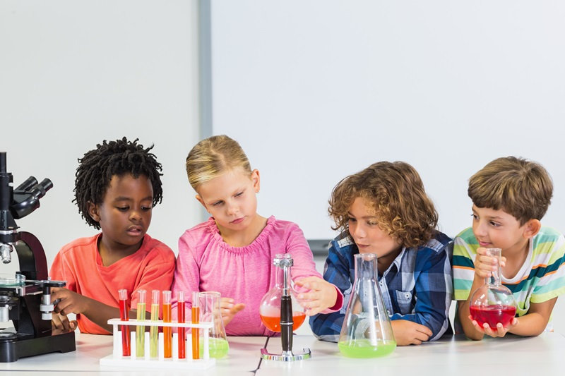 A group of young students sit at a school table with various science equipment