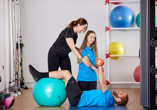 A patient of Exercise Physiology at UC Health Clinics using an exercise ball and free weights.