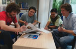 Students sitting around a table looking at magazines