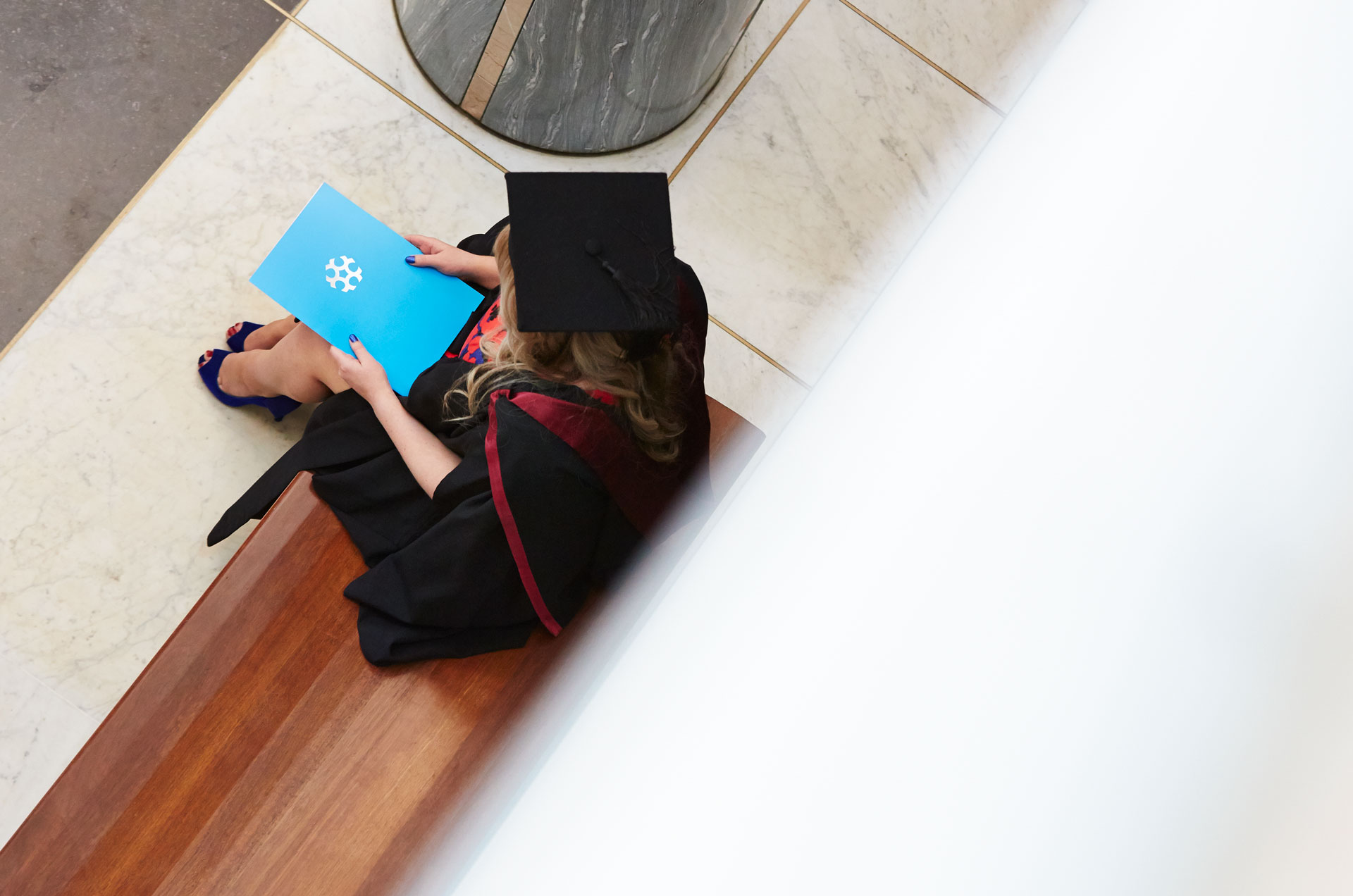 A graduate in a graduation gown sits with her University of Canberra folder