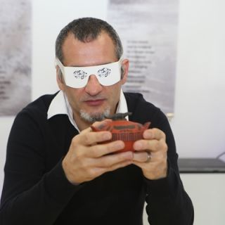 PhD Student Beaux Guarini wears a pair of paper spectacles which simulate a vision impairment while holding his 3D-printed sugarbowl.