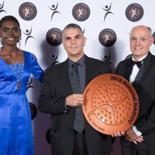Professor Sarra holds a large circular bronze award, on either side are Magnolia Maymuru and Robert Annis-Brown