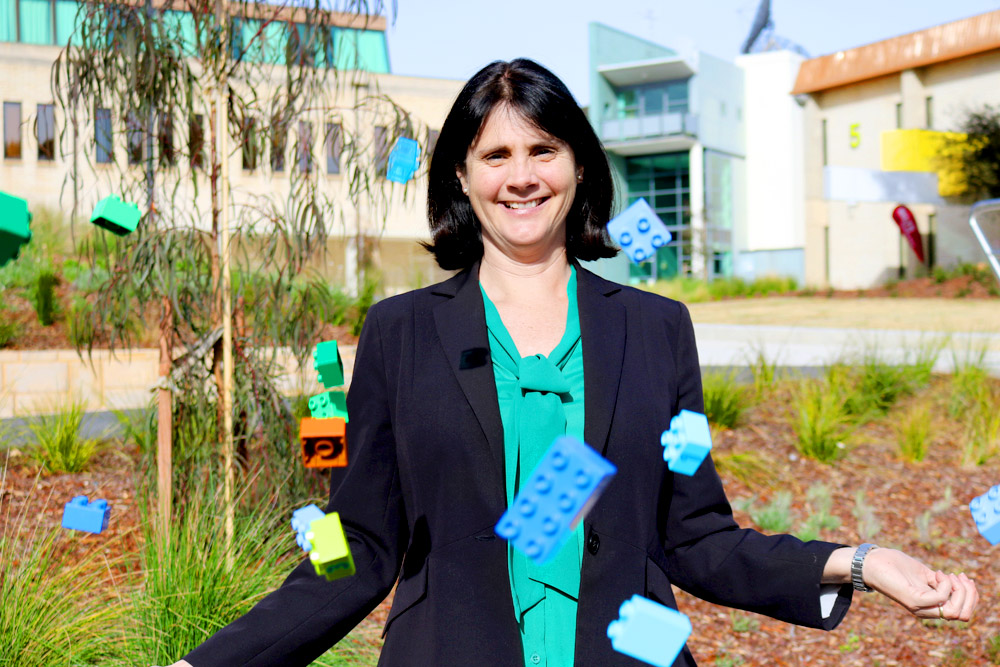 Dr Kim Simoncini stands on the UC Concourse with colourful Duplo blocks raining around her