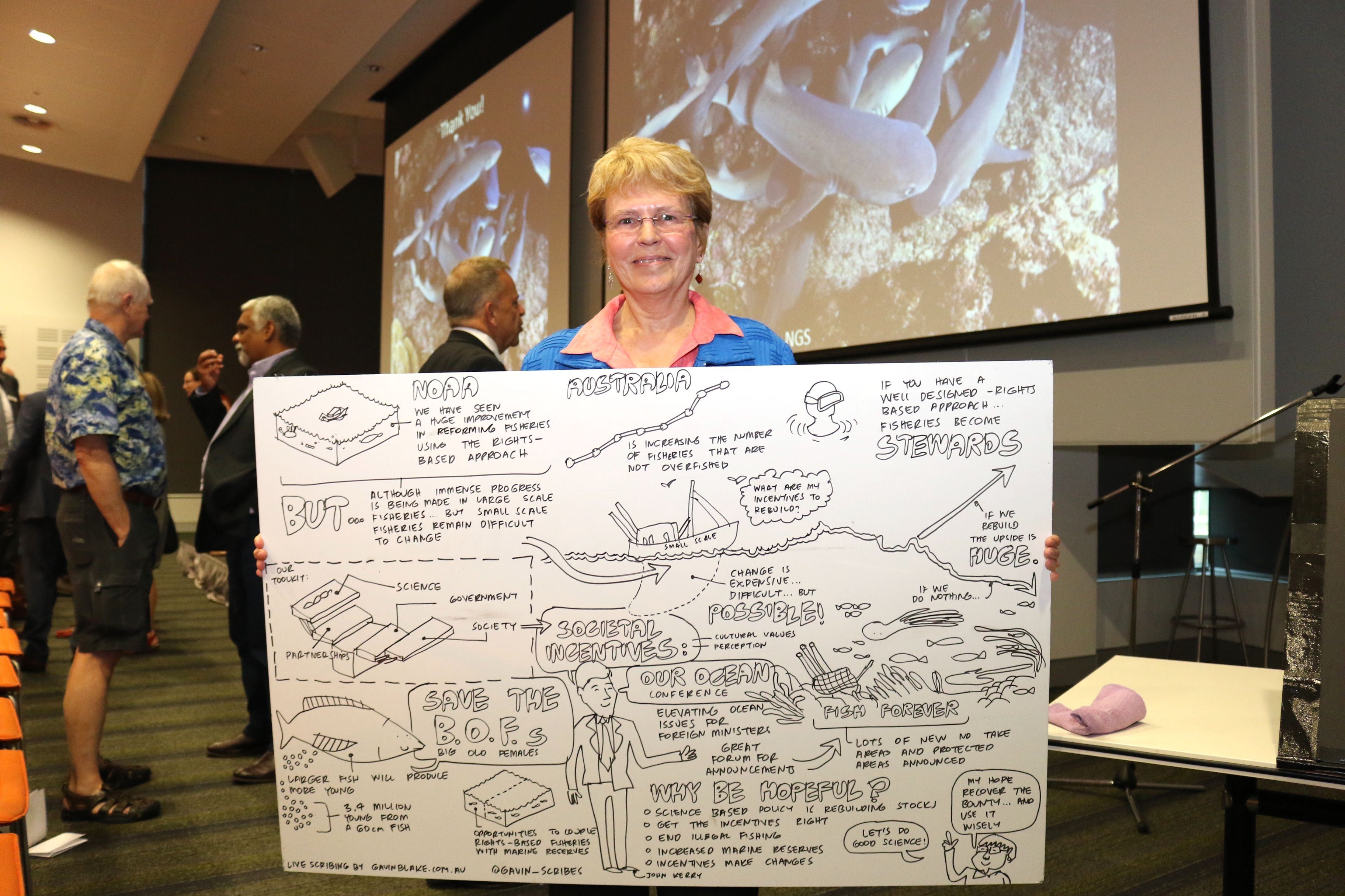 Professor Lubchenco poses with the visual sketch of her lecture by scribe Gavin Blake