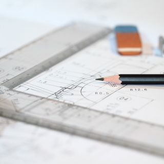 An architects drawing board, with rulers, pencils and schematics