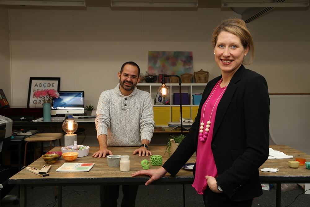 Carlos Montana Hoyos and Lisa Scharoun stand in the Cross-Cultural Design Lab, with a sample of works on a table between them