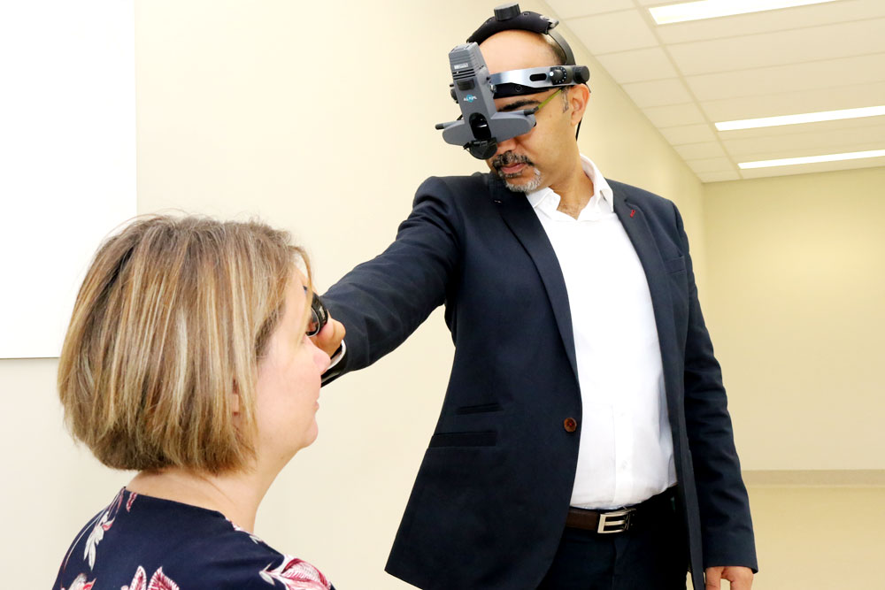 Assistant Professor of Optometry Ron Sabeti examines the eye of the head of the School of Optometry Nicola Anstice