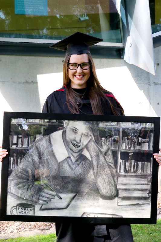 Erin-Louise Hagerty holding a charcoal sketch of herself.