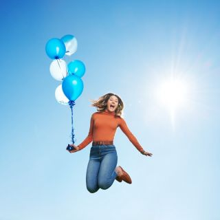 Girl jumping with balloons