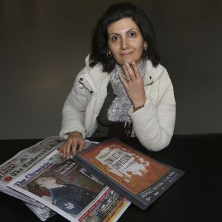 Dr Mona Soleymani sits in front of newspapers