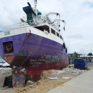 A boat washed ashore by Typhoon Haiyan, graffiti on the side reads 'we need foods, rice and water.'