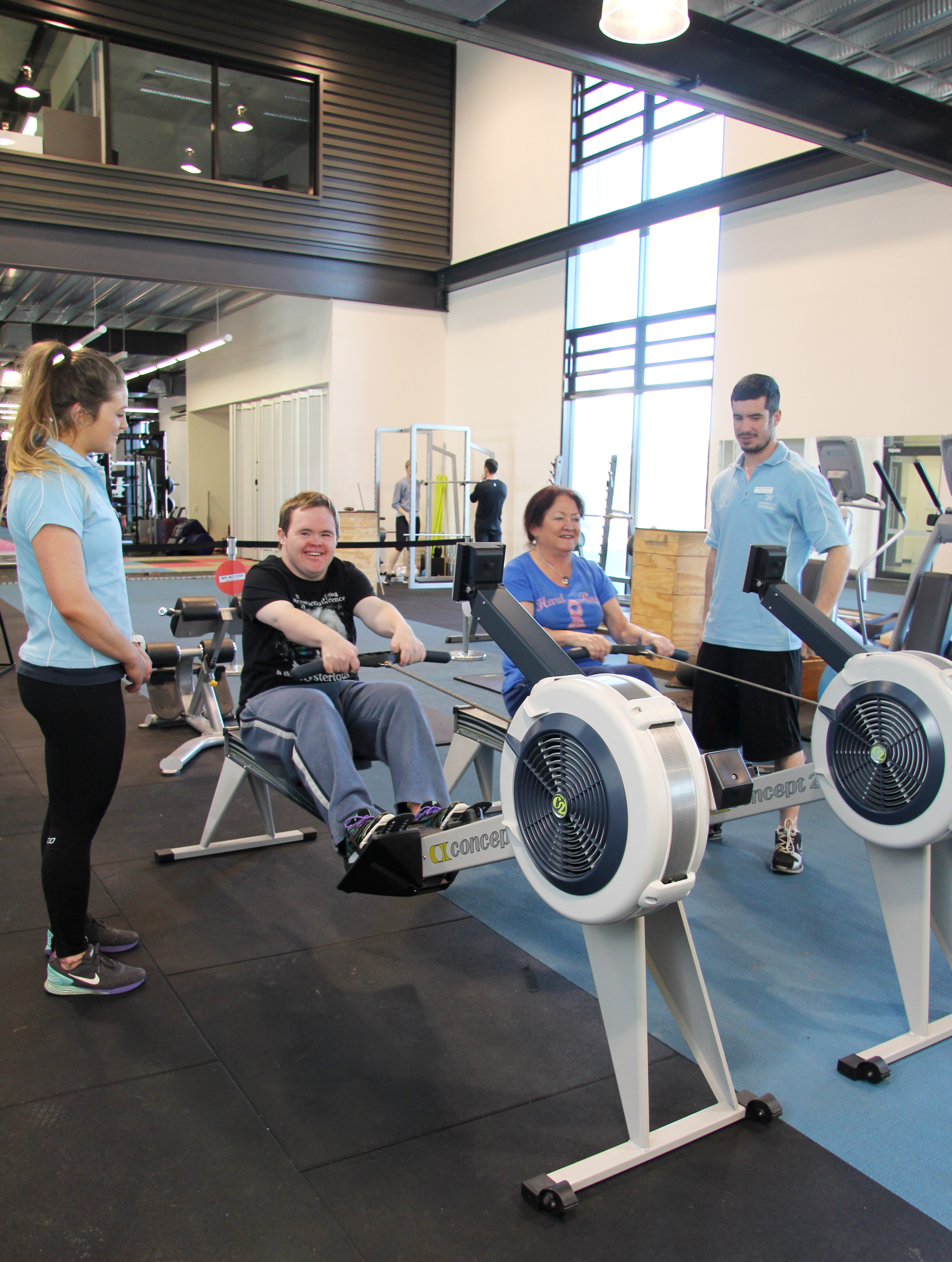 The mother and son enjoying using the rowing machines in the Sporting Commons under the guidance of the UC students