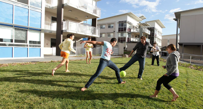 Image of students playing a casual game of football on campus grounds