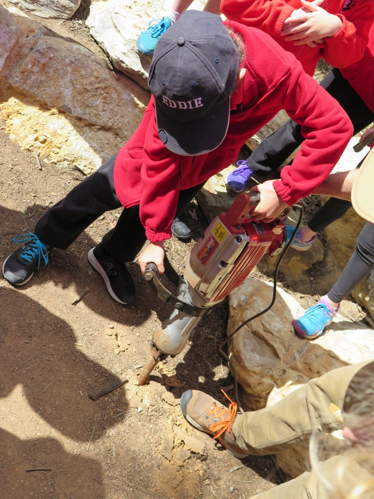 A student tests out the jackhammer in the playground at Aranda Primary School
