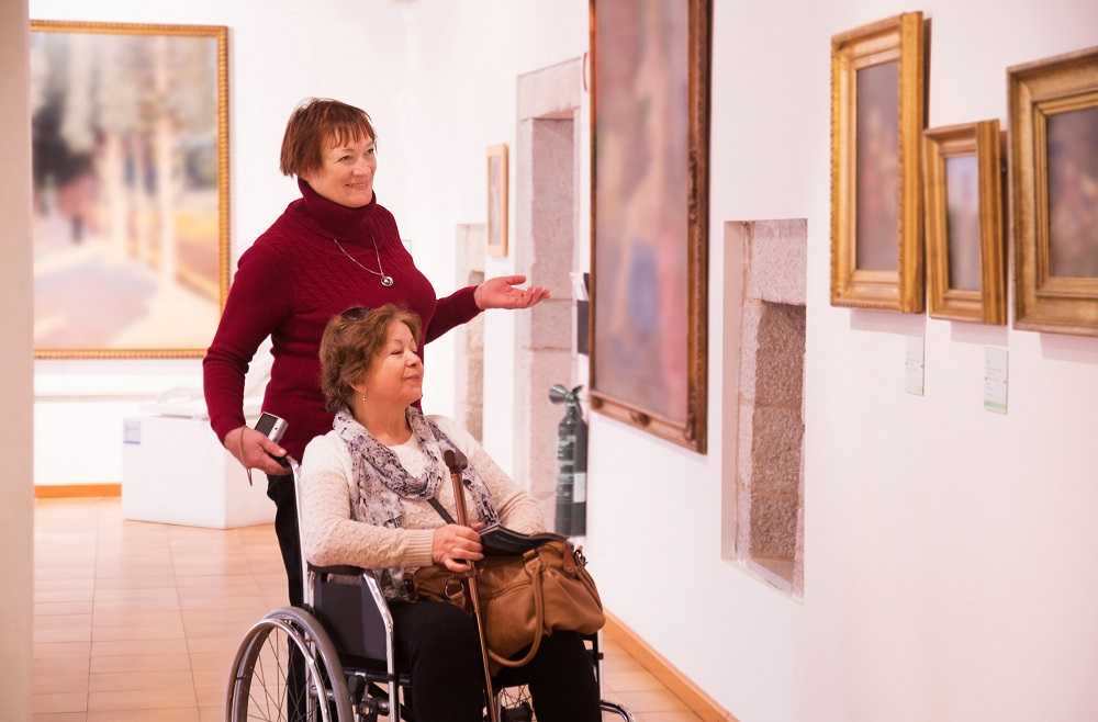 Two women, one using a wheelchair, visit an art gallery