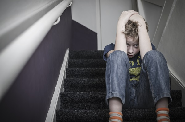 A scared looking young boy with his head in his hands, sits on a flight of stairs