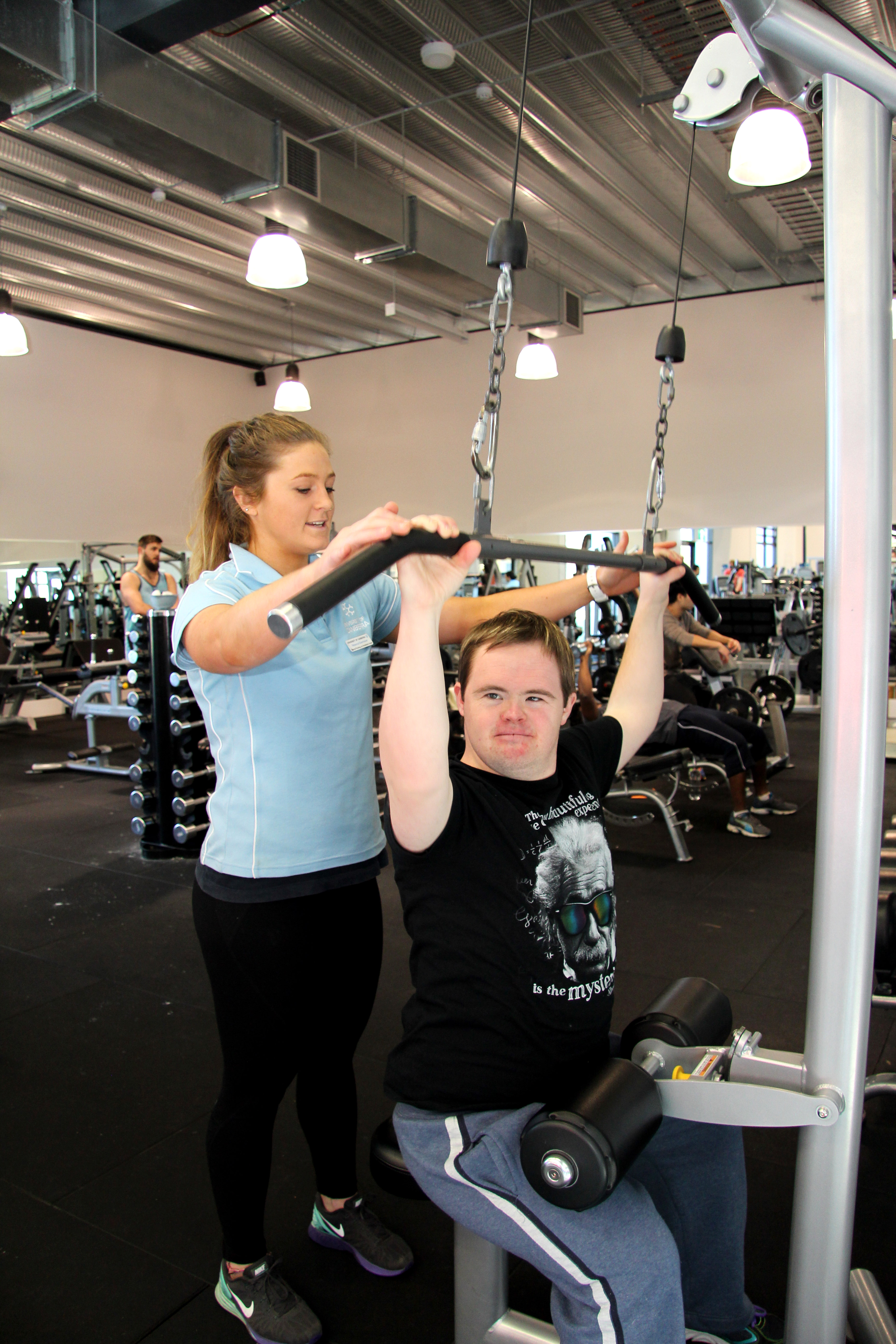 Student Rebecca Eisenhauer showing Daniel Brown from the Special Olympics how to use the gym equipment