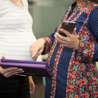 Two pregnant women talking while using smart-technology devices