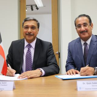 Professor Deep Saini and Dr Qais Saleh AL-Duwairi sign the MOU document with Australian and Kuwaiti flags on their desk