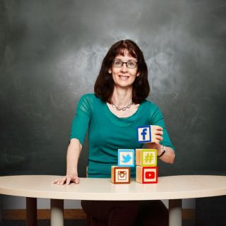 Centenary Research Professor Deborah Lupton sits at a desk with Social Media-themed building blocks