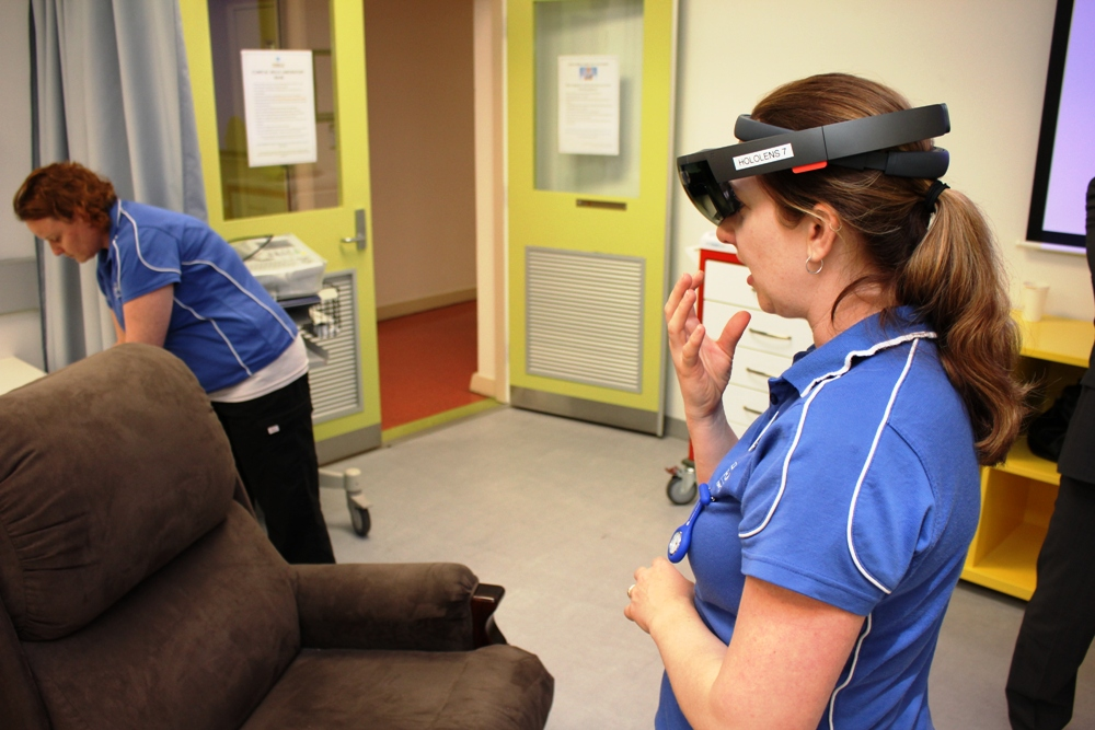 Nursing students wearing the HoloLens look at an empty chair where a patient avatar appears