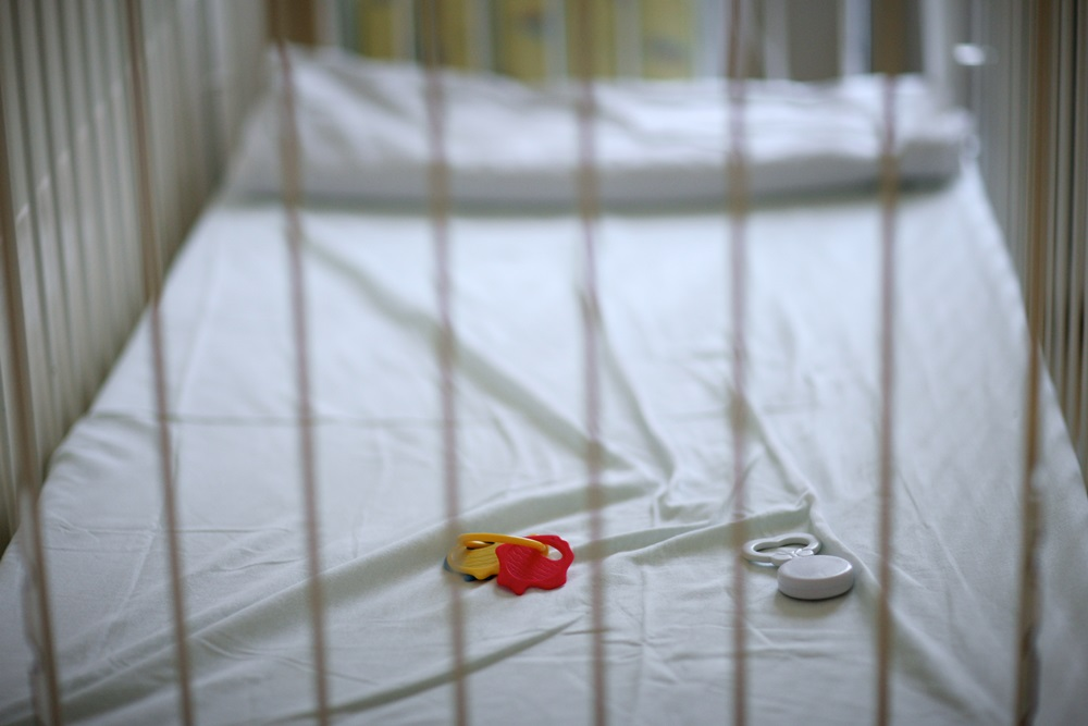 An empty cot with a small baby's rattle