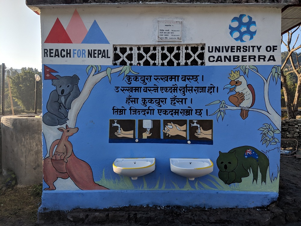 The UC students developed a poster to outline the four steps of proper hand-washing, at the amenities block which they also helped to refurbish. The words to Kookaburra, the classic Aussie nursery rhyme were translated into Nepali script, and the children would sing every time they washed their hands. Photo: Lachhu Thapa/REACH For Nepal